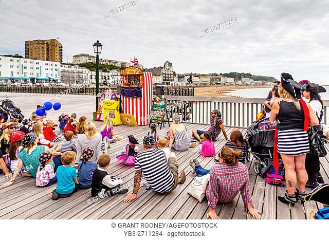 People Watch A Traditional Punch and Judy Show On Hastings Pier, Hastings, Sussex, UK