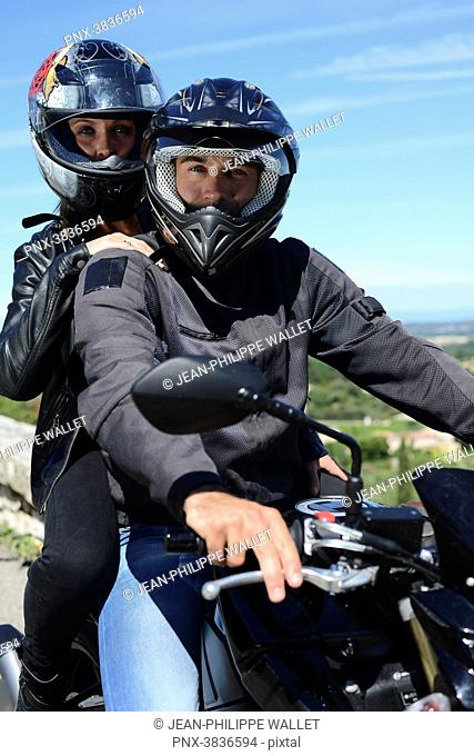 Happy young biker couple riding motorbike in summer