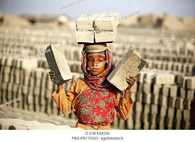 Girl child worker carrying bricks on her head at Fatullah Narayanganj, Bangladesh February 2011