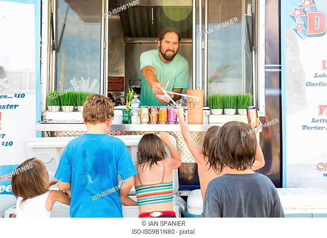 Group of children queuing at fast food trailer
