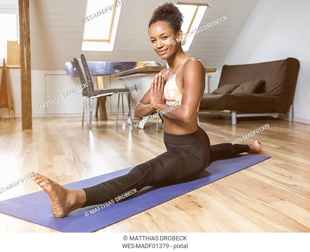 Portrait of smiling young woman in yoga pose doing splits