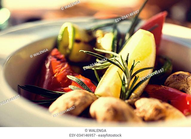 fresh salad with tomatoes, mushrooms, lemon and rosemary on the plate wooden table. Autumn concept