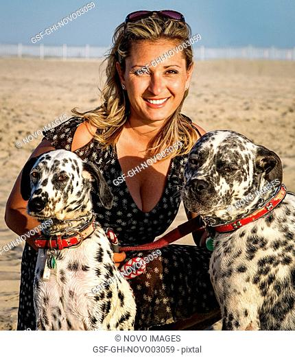 Portrait of Blonde Woman with Two Dalmatians on Beach