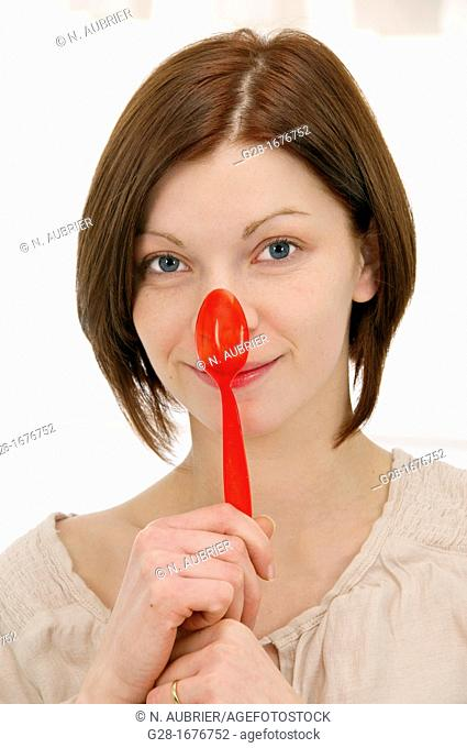 young smiling woman in beige, holding a red plastic teaspoon over her nose