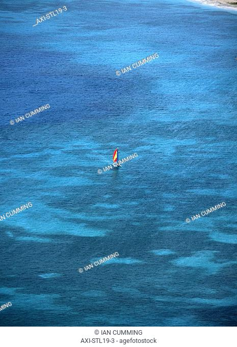 Small catamaran sailing in the shallow waters,Reduit Beach, Rodney Bay as seen from the top of the fort, Pigeon Island, St Lucia
