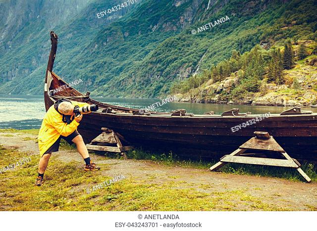 Male tourist with camera taking photo of old wooden viking boat on seashore in norwegian nature, foggy misty day. Mountains and fjord Sognefjord
