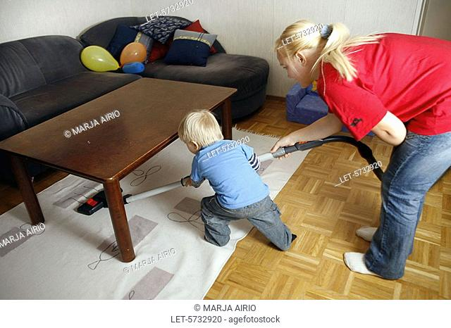 A mother and a two-year-old little boy are hoovering at home