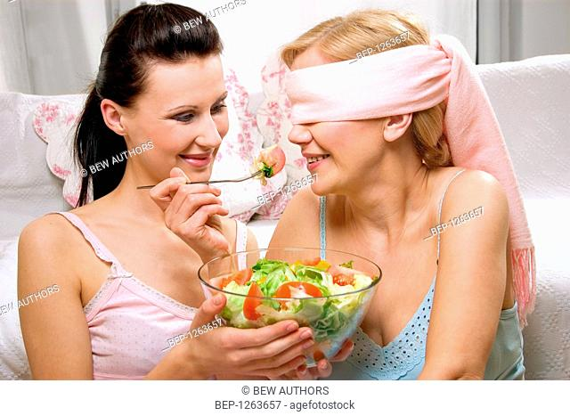 Mother and daughter while eating salad