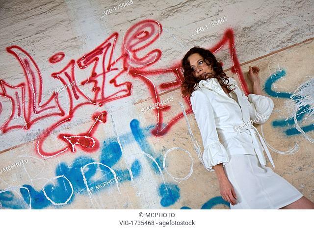 young dark-haired woman posing at wall with graffiti - 05/07/2008