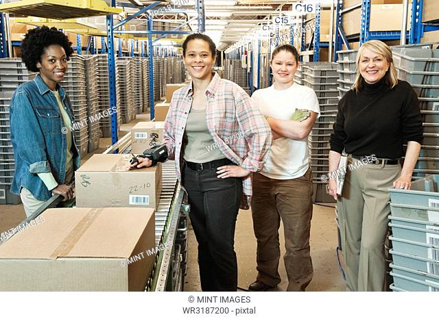 Team portrait of multi-ethnic female warehouse workers working next to a motorized feed conveyor in a large distribution warehouse