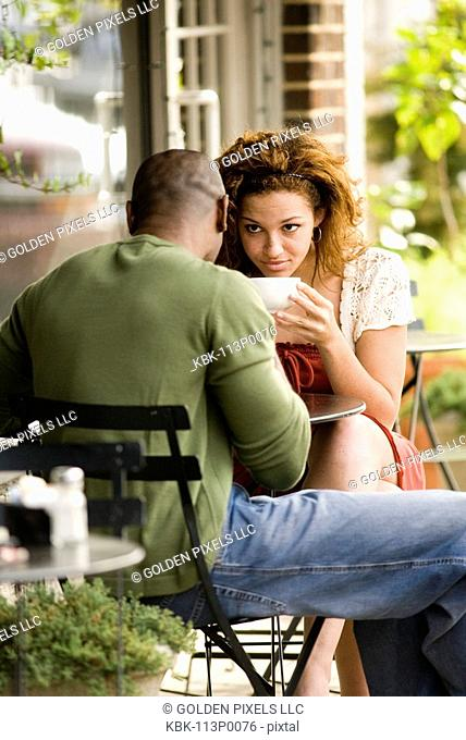 Close-up view of young couple sitting at a table at a sidewalk cafi