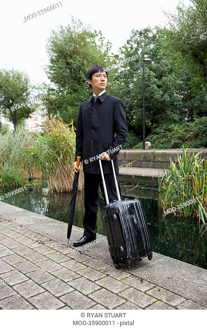 Full length of Asian businessman with luggage standing by pond