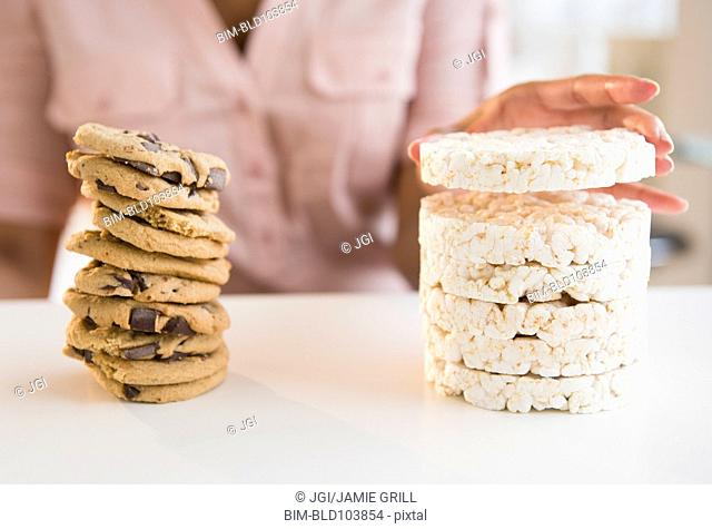 Cape Verdean woman stacking cookies and rice cakes