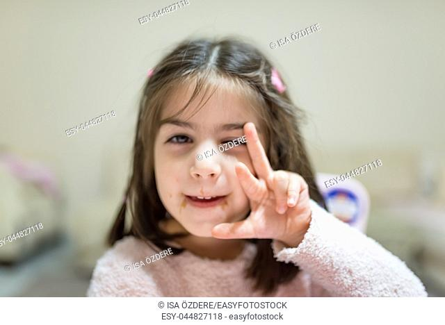 Little cute girl with dirty funny face after eat surprise chocolate while looking at camera