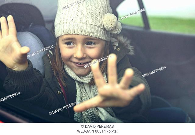 Portrait of happy little girl with wool cap putting her fingers on car window
