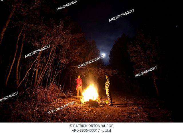 Two males standing around a fire while camping in Colorado