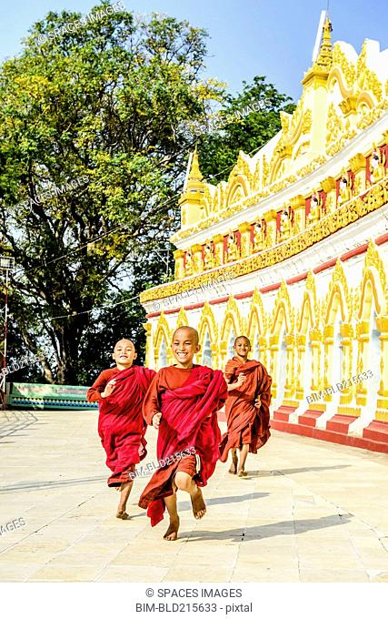 Asian monks-in-training running outside ornate temple