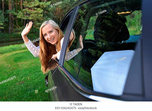 Smiling woman sit in car.car stands on green glade