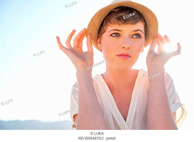 Woman holding her hat down by its rim