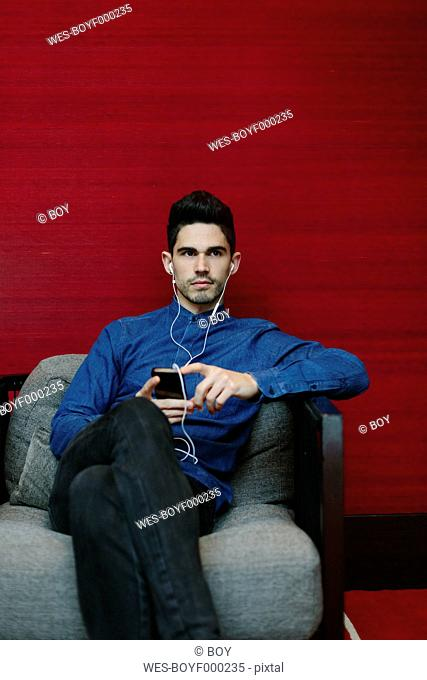 Young businessman sitting on armchair of a lobby hearing music with earphones