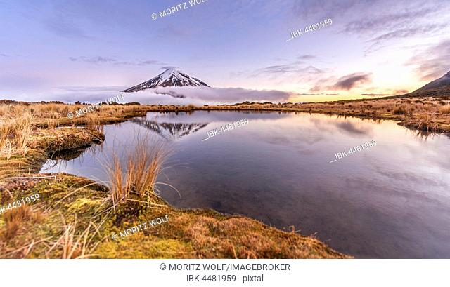 Reflection in Pouakai Tarn lake, clouds around stratovolcano Mount Taranaki or Mount Egmont at sunset, Egmont National Park, Taranaki, New Zealand