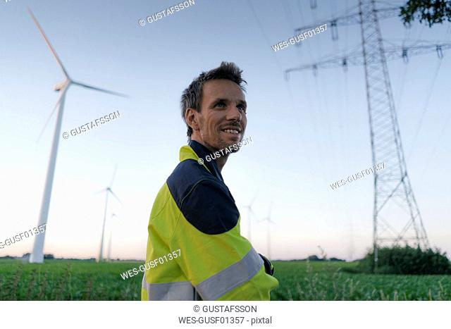 Smiling engineer next to a wind farm and power pole