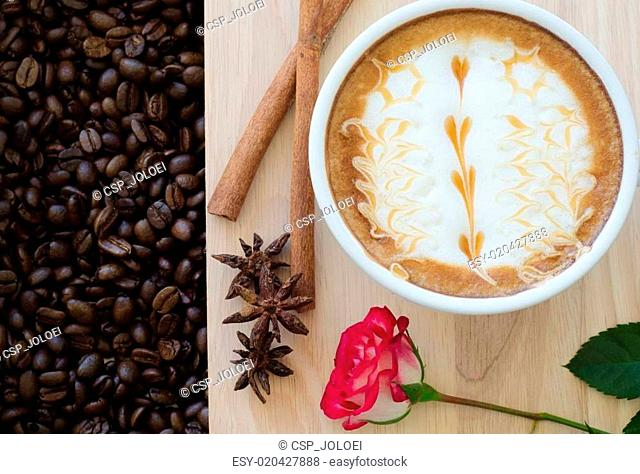 a cup of latte art on wooden and coffee bean background
