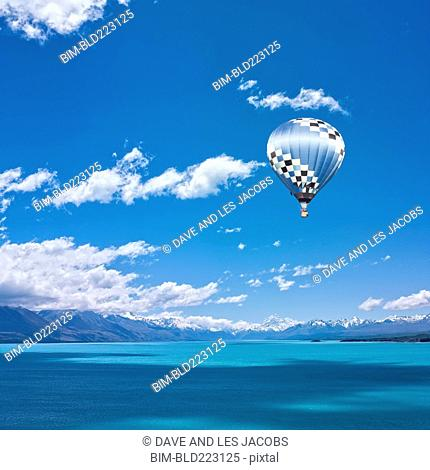 Hot air balloon over snow-covered mountains and lake