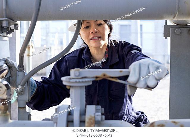 Female power engineer adjusting pressure valve at power station