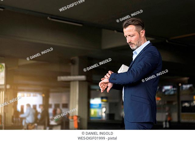 Businessman waiting at bus terminal checking the time