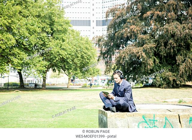 Businessman in city park wearing headphones and using tablet