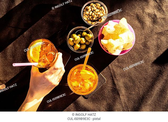 Overhead view of sidewalk cafe table with woman's hand holding aperitif, Riccione, Emilia-Romagna, Italy