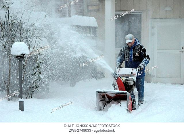 Man with snowblower clearing snow