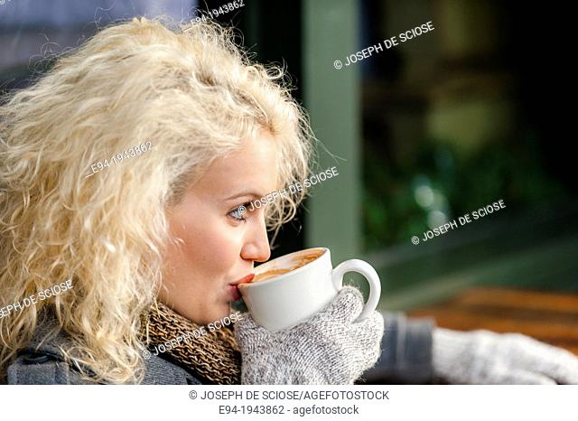 A 22 year old blond woman sitting at an outdoor cafe with a cup of coffee in the winter