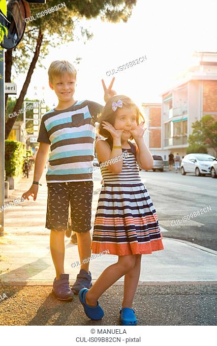Brother and sister in street showing off for camera