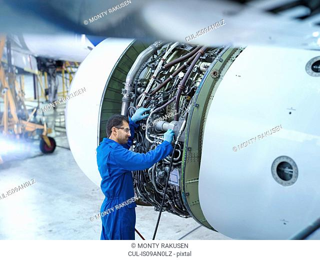 Engineer working on jet engine in aircraft maintenance factory