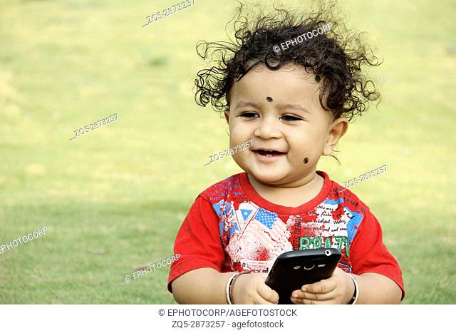 Little child with mobile in hand looking and smiling