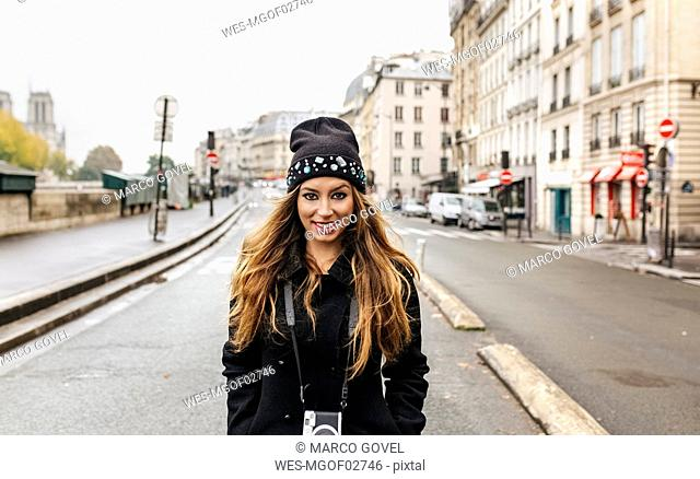 France, Paris, portrait of smiling young woman on the street