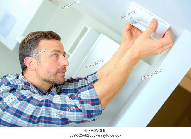 Man fitting an air vent