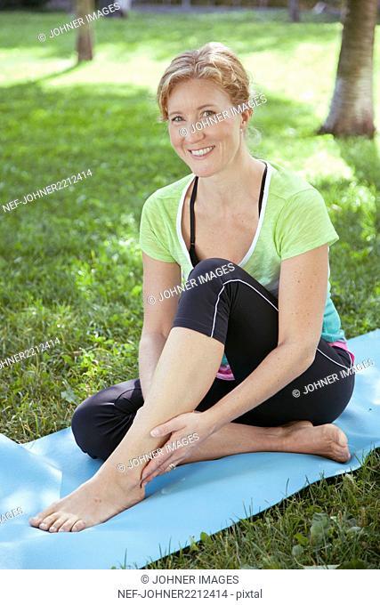 Smiling woman on exercising mat