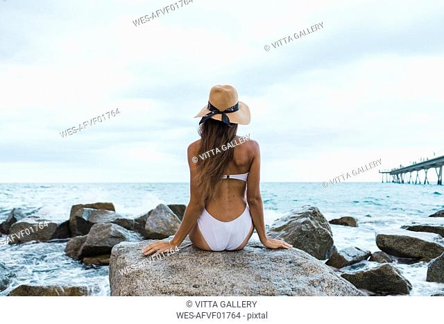 Rear view of young woman wearing swimsuit and hat sitting on rock in the sea