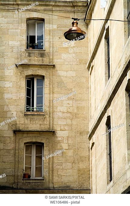 Lantern hanging from a wire with apartment buildings in the background, Bordeaux, France