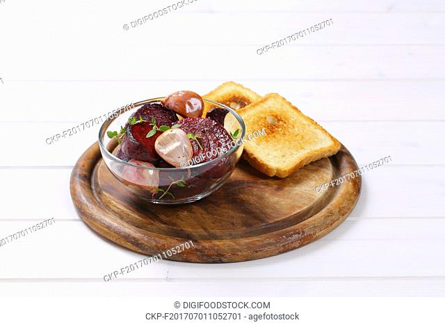 bowl of baked beetroot and garlic with toasted bread on round wooden cutting board