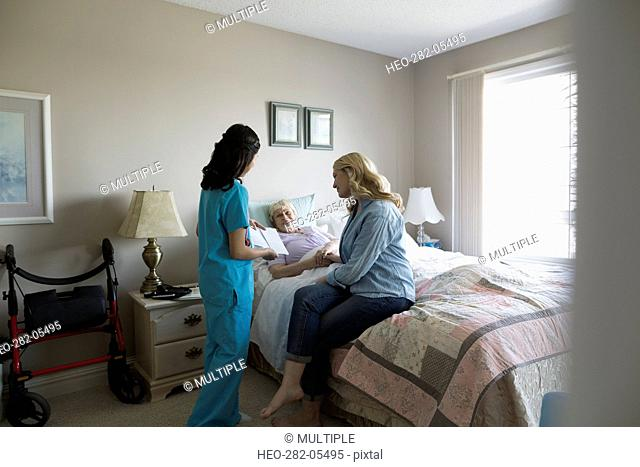 Home caregiver talking to senior woman and daughter in bedroom