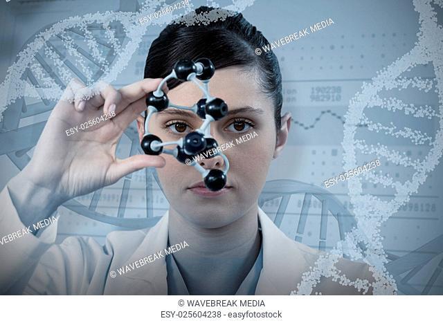 Composite image of female scientist looking through molecular model