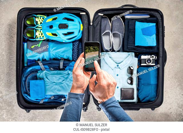 Overhead view of man's hands using smartphone touchscreen above packed suitcase with blue bike helmet, backpack, retro camera and shirt