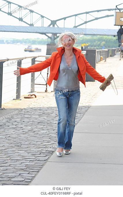 Older woman walking along riverfront