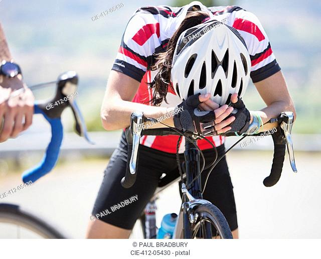 Disappointed cyclist resting on handlebars