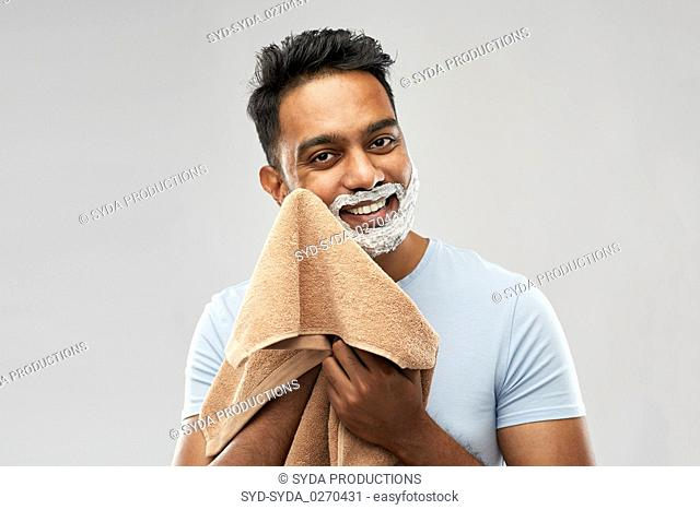 man removing shaving foam from face by towel