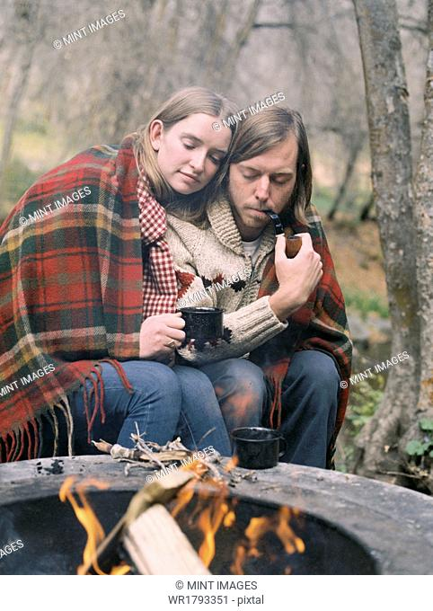 Young couple sitting by a fire pit, wrapped in a blanket
